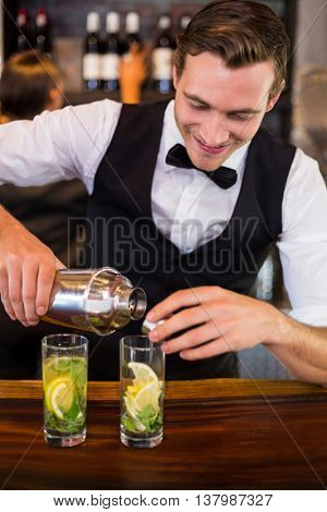 Bartender pouring a drink from a shaker to a glass on bar counter in bar