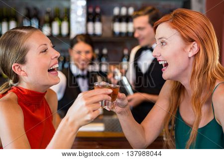 Happy friends holding a tequila shot in front of bar counter in bar
