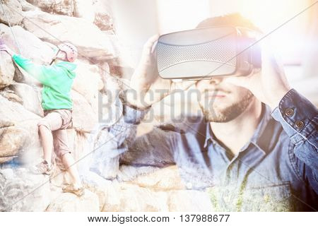 Focused man climbing a large rock face against man wearing virtual glass