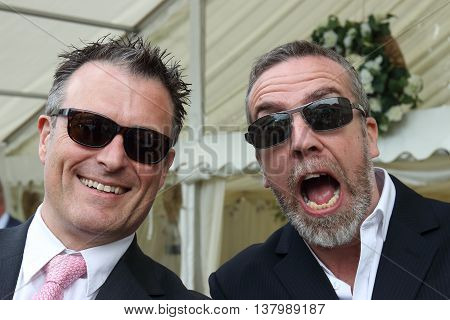 2ND JULY 2016,PORTSMOUTH,ENGLAND: Two English men wearing sunglasses and suits for a wedding in Portsmouth, England, 2nd july 2016