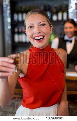 Portrait of happy woman holding a tequila shot in front of bar counter in bar