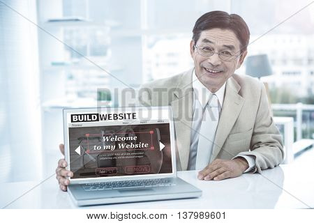 Composite image of build website interface against smiling asian businessman showing his laptop