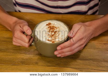 Woman drinking a hot beverage in the cafe