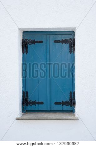 Pair of closed blue wooden shutters set in a whitewashed wall