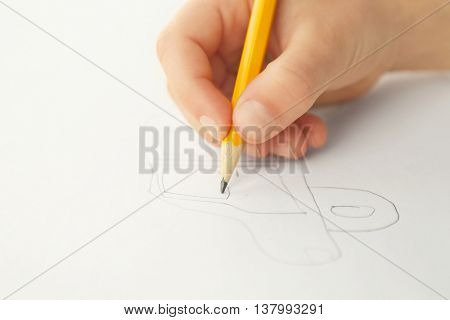 Child's hand drawing picture on paper