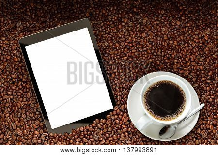 Tablet computer with blank white screen and cup of coffee on pile of coffee beans