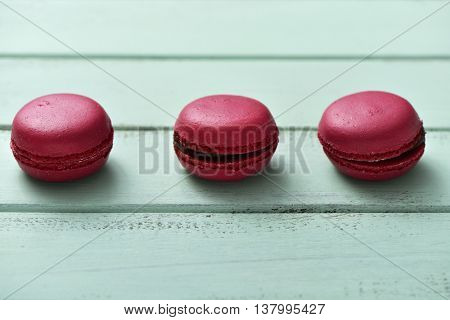some appetizing red macarons on a blue rustic wooden surface