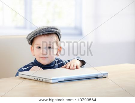 Adorable ginger little boy wearing cap, playing with laptop at table.