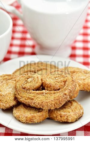 some palmier pastries made with spelt flour in a white ceramic plate on a table set with a red and white checkered tablecloth