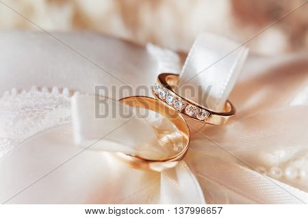 Golden wedding rings with diamonds on fabric. Wedding jewelry details. Engagement ring with precious gemstones.