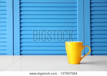 Cup on blue folding screen background