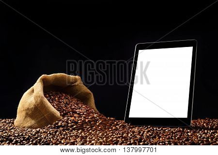 Tablet computer with blank white screen and coffee beans in burlap sack on black background