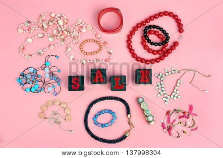 Black wooden cubes with female accessories on pink background. Sale concept
