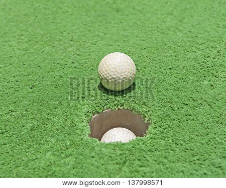 Closeup detail of golf ball by hole on green artificial grass astroturf