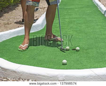 Man in flip flop sandals on summer vacation playing mini golf putting ball at hole