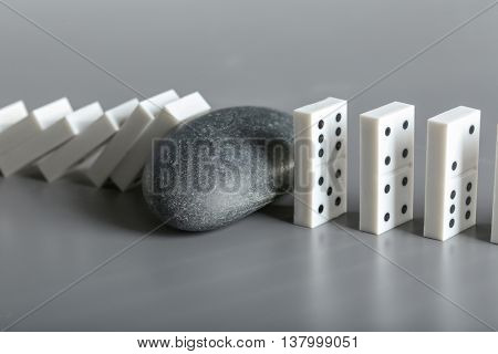 Dominoes and stone on grey background