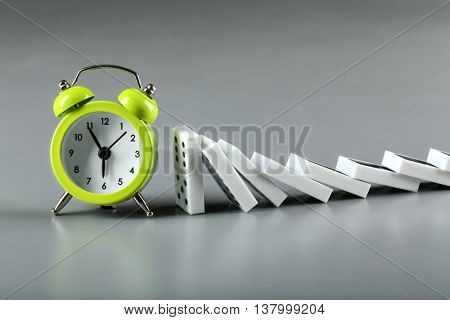 Dominoes and alarm clock on grey background