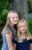 stock photo of pre-teen  - Image of lovely young sisters in a park in front of a tree - JPG
