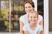 Mother and smiling daughter sitting outside the house. Happy mom and little girl enjoying in a summe poster