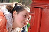Girl Looking At Hole Of Red British Postbox poster