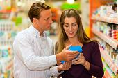 foto of grocery-shopping  - Couple in a supermarket shopping groceries and other stuff - JPG