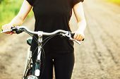 Постер, плакат: Detail Of A Bicycle Woman Riding Her Bicycle Bicycle On Road