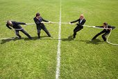 Businessmen and businesswomen playing tug of war