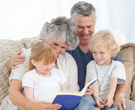 pic of family vacations  - Family looking at a photo album in the living room - JPG