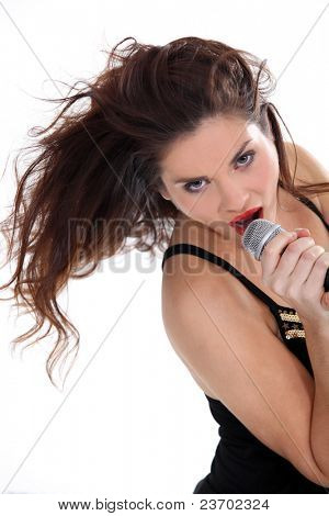 Attractive brunette singing into microphone