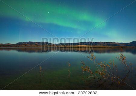 Northern lights y colores de otoño en el lago tranquilo