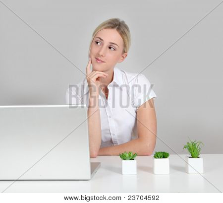 Blond woman sitting by computer and green plants