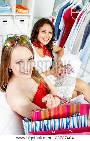 Retrato de clientes felizes com sacos olhando câmera depois das compras