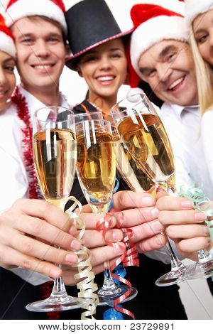 Image of crystal glasses full of champagne held by happy business people