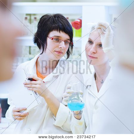 two female researchers in a chemistry lab (color toned image; shallow DOF)
