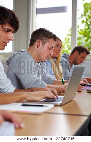 Student Taking Notes At Laptop