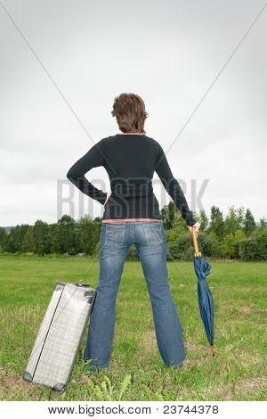 Woman On The Grass With Suitcase And Umbrella