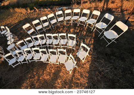 White Wooden Chairs In Field With Hay Bails