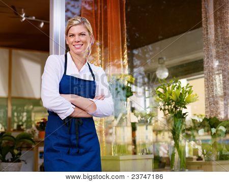 Jovens bonitas mulher que trabalha como florista em loja e sorrindo
