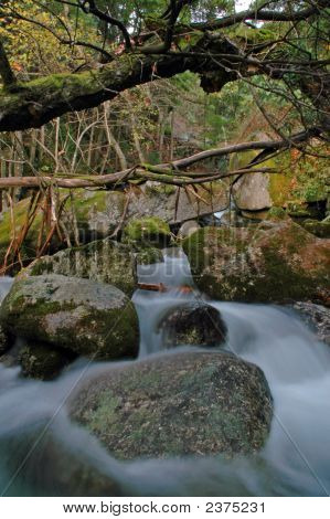 Beautiful Waterfall Between Rocks Covered By Moss And Leaves In Outumn
