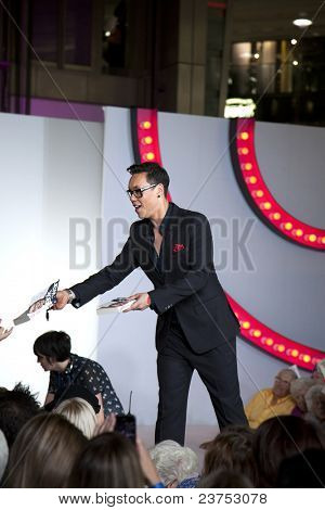 "SOUTHAMPTON, UK - SEPT. 22: Gok Wan signs copies of his autobiography from the catwalk in West Quay Shopping Centre during filming of his television show ""Gok's' Clothes Roadshow"" on September 22, 2011 in Southhampton, UK."