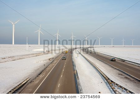Dutch Highway In Wintertime With  Wind Turbines Behind It