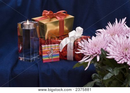 Gifts And Candle Behind Flowers