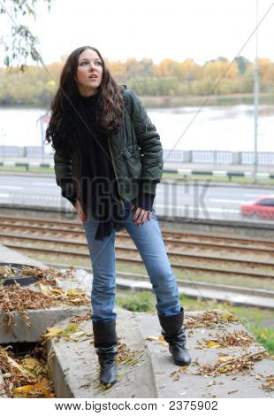 Young Model With Dark Hairs On River Bank. Fall. Autumn