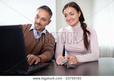 Beautiful woman sitting with a man using laptop