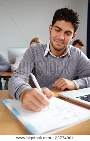 Student Taking Notes In University Class