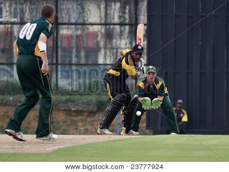 PUCHONG, MALAYSIA - SEPT 24: Tom Kimber, Guernsey watches R. Madhavan, Malaysia bat in this Pepsi ICC World Cricket League Div 6 finals at the Kinrara Oval on September 24, 2011 in Puchong, Malaysia.