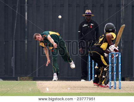 PUCHONG, MALAYSIA - SEPT 24: Adam Martel of Guernsey bowls Malaysia's Faris Lee at the Pepsi ICC World Cricket League Div 6 finals at the Kinrara Oval on September 24, 2011 in Puchong, Malaysia.