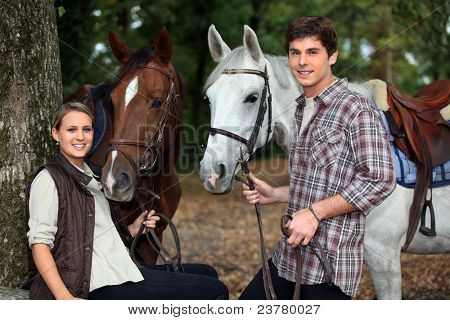 young couple and horses in forest