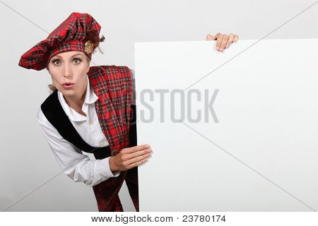 Surprised woman in traditional Scottish outfit with a board left blank for your message