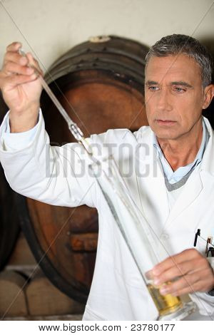 Man testing brandy in a cellar
